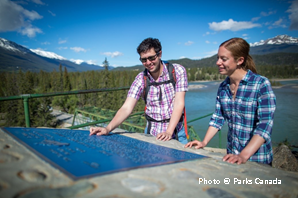 Visitors reading the Athabasca Canadian Heritage River designation plaque in Jasper National Park, Alberta.