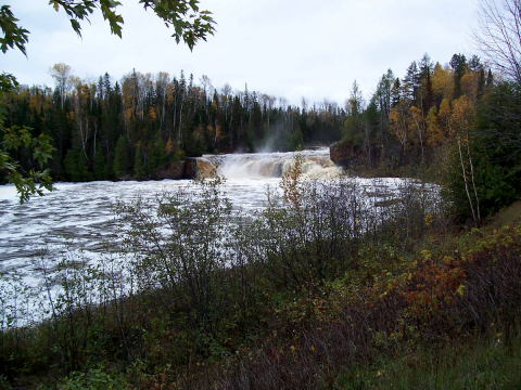 Middle Falls flowing over a small vertical drop with colourful autumn trees lining the shore.