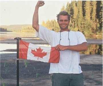 Young Canadian man proudly holding the Canadian Flag at Clearwater River, Alberta